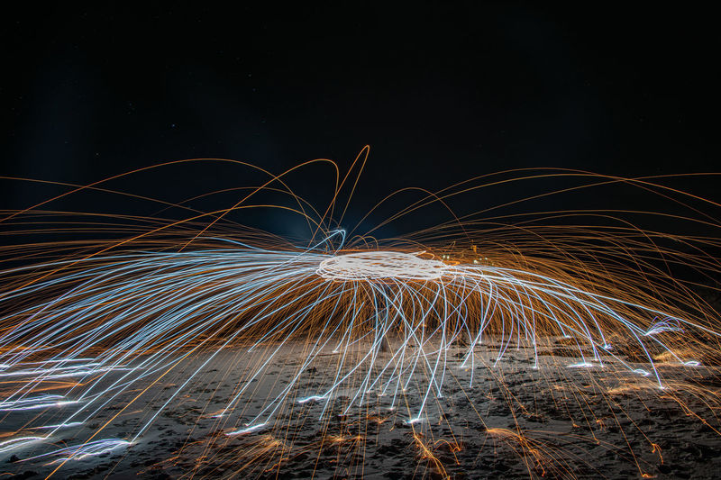 Person spinning wire wool at night