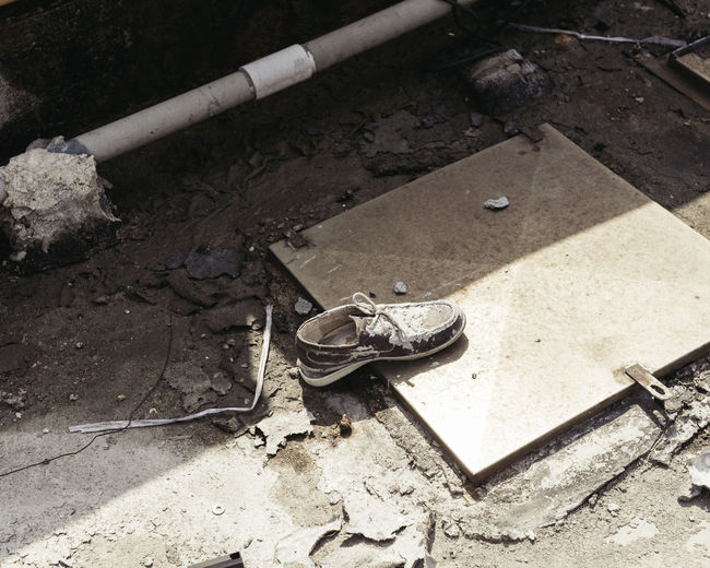 High angle view of shoe on manhole at street