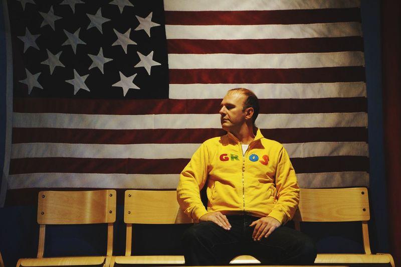 Man Sitting On Chair Against American Flag