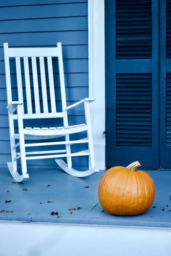 View of pumpkins and chair on table against building