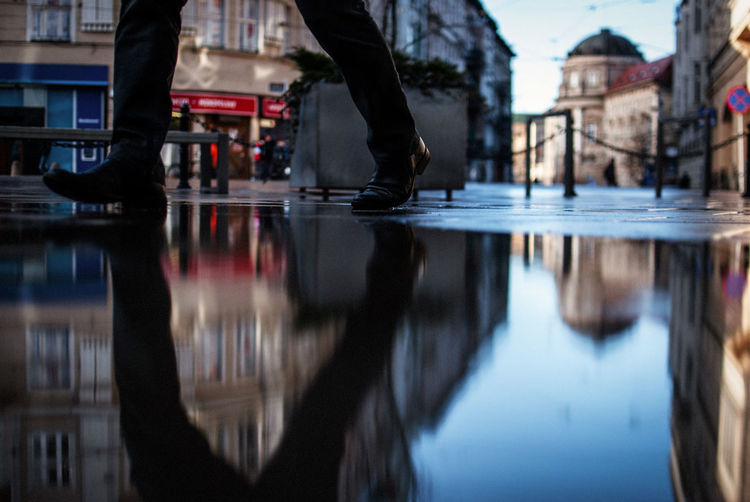 Surface level of man walking by puddle on footpath in city