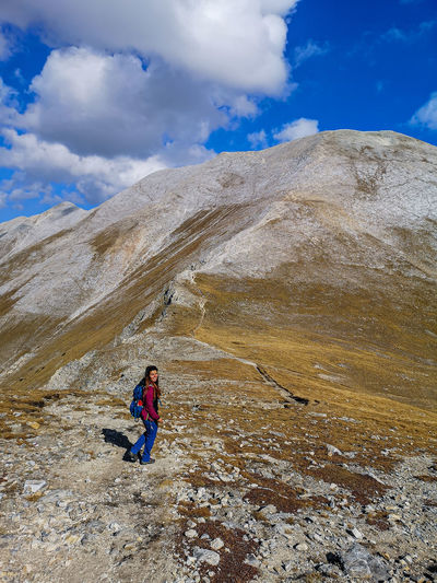 Full length of person on rock in mountains against sky
