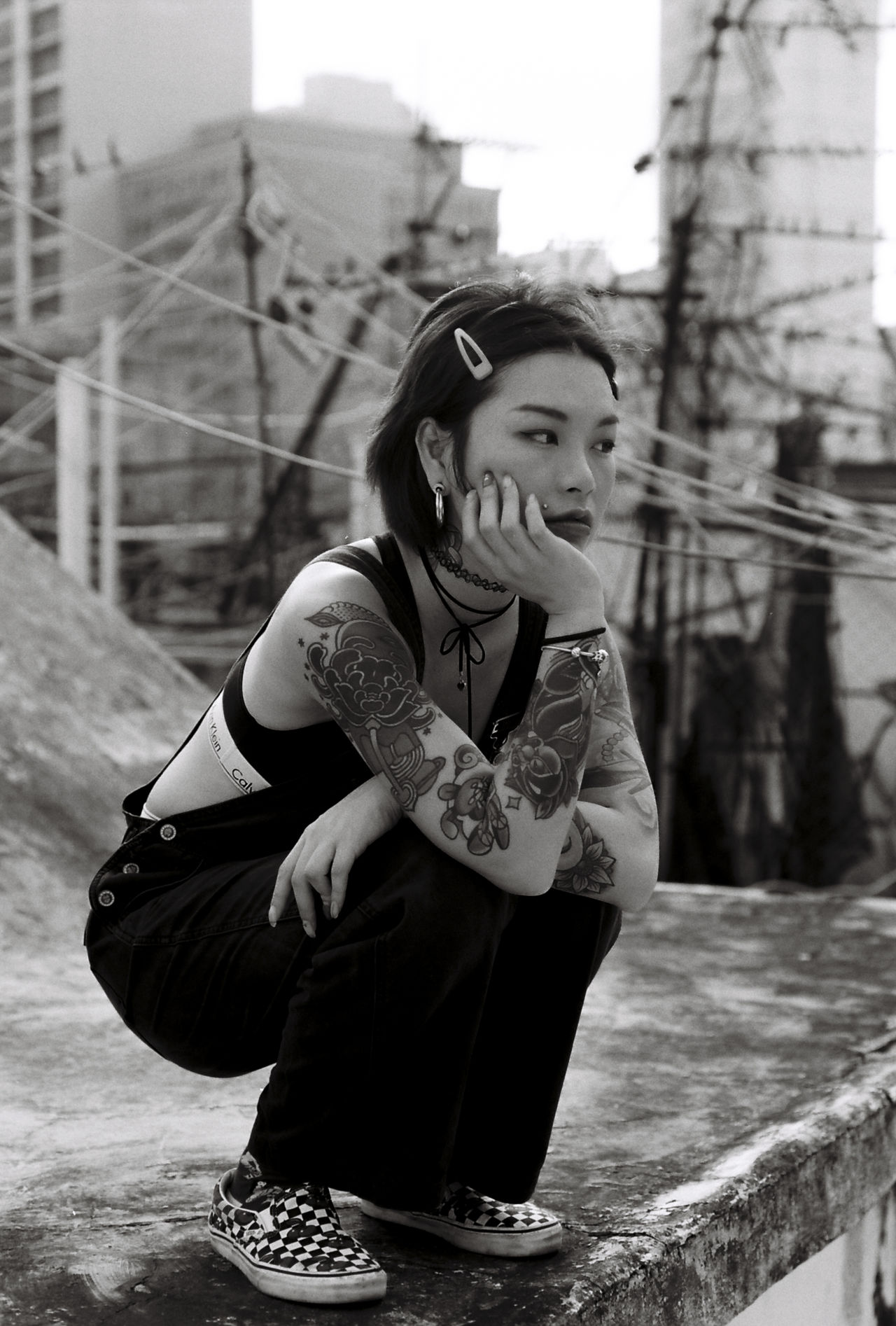 Thoughtful young woman with tattoos crouching on retaining wall at building terrace