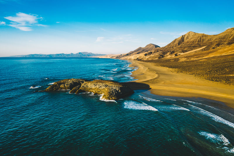 Aerial View Panorama Of Cofete Beach Valley In Fuerteventura shot in the evening time during sunset. Cofete Beach Valley Fuerteventura Canary Islands Sunset Evening Shore Coast Coastline Mountains Wild Atlantic Ocean Cinematic Nature SPAIN Landscape Travel Sand Island Scenic Sky Mountain Water Summer Beautiful Vacation Desert Blue View Background Holiday Scenery Sunny Cofete Beach Canary Island Europe Volcanic  Tourism Waves Sandy Fuerteventura Beach Seascape Drone  Aerial Panorama Golden Dusk