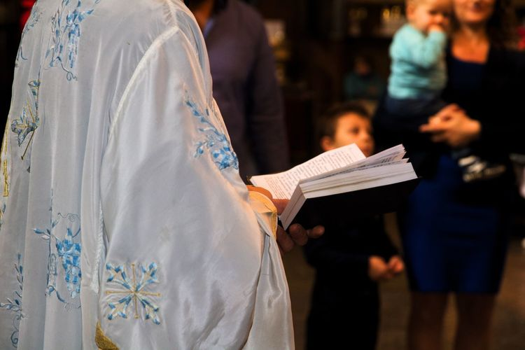 Midsection of priest reading bible by people in church