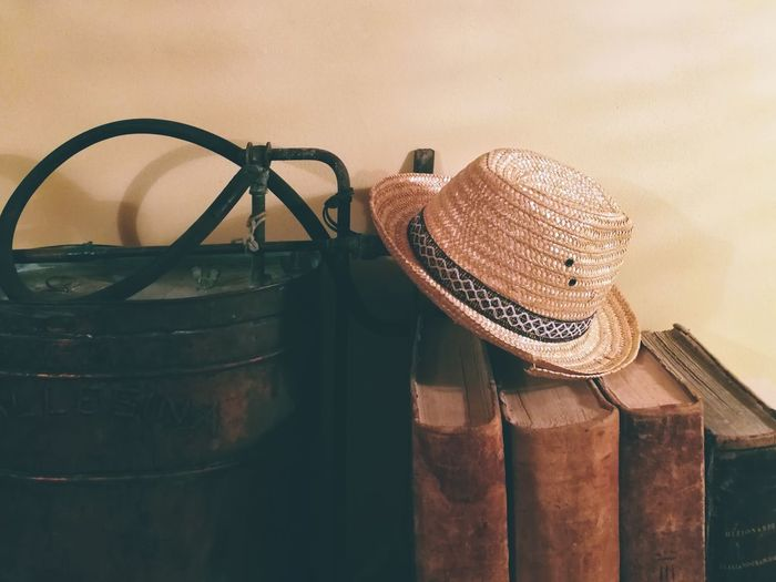 Close-Up Of Wicker Hat On Book Against Wall