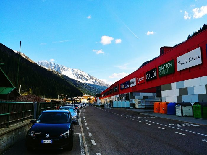 Cars on road by mountain against blue sky