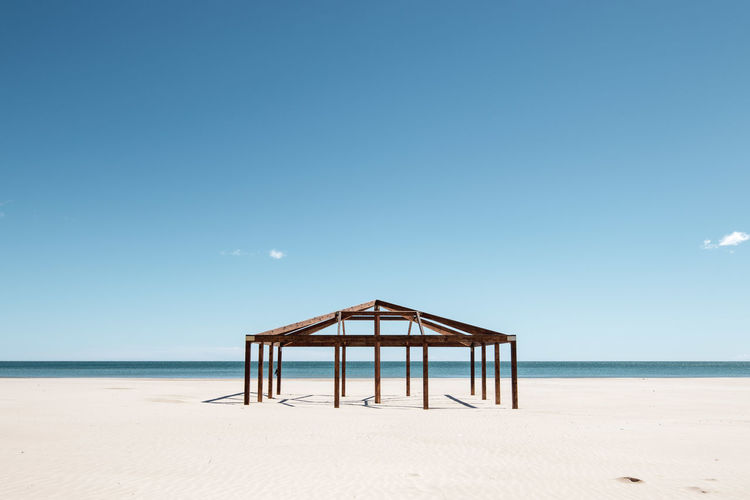 Gazebo at beach against clear blue sky