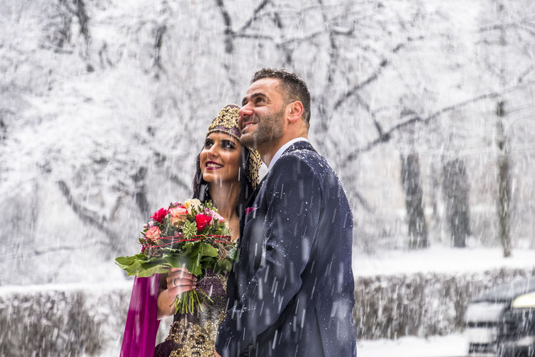 Happy couple in traditional turkish wedding dress during their wedding in a snow storm Asian  Bond Diva♥ East Fashion Gold Love Ottoman Pink Princess Princess ♥ Sultan Turkey Wedding Winter Ceremony Fabric Purple Robe Smiling Snow Togetherness Traditional Turkish Velvet