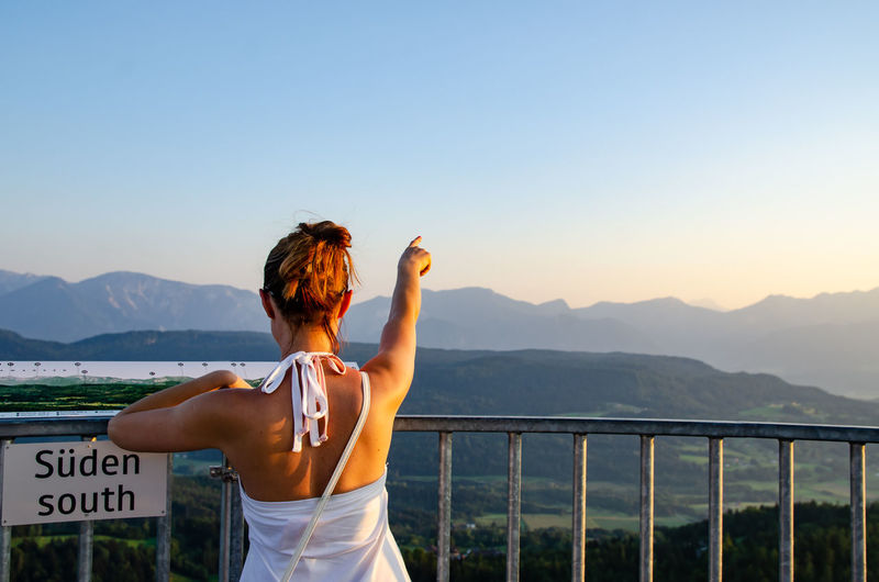 Rear view of woman pointing at mountains