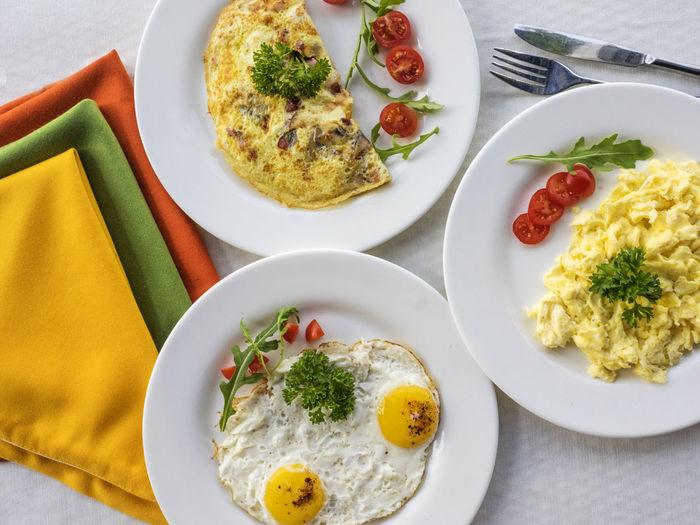 Omelets and frying eggs on the table Frying Breakfast Close-up Day Egg Egg Yolk Eggs Food Food And Drink Fork Freshness Fried Egg Garnish Healthy Eating High Angle View Indoors  No People Omelet Omelets Plate Ready-to-eat Serving Size Table Vegetable Yellow