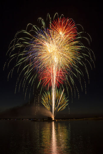 Low angle view of firework display by lake against sky
