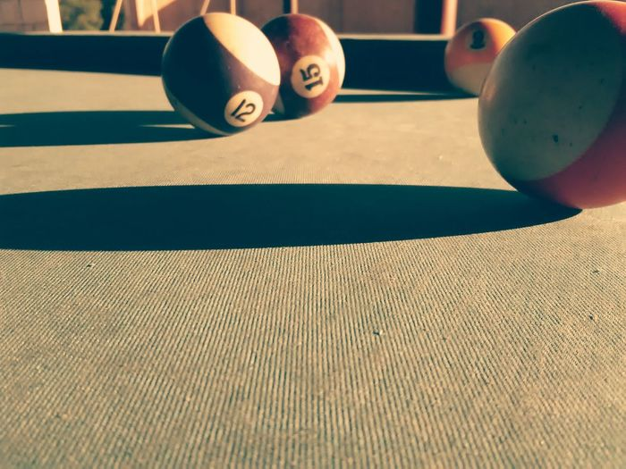 Close-up of pool balls on table during sunny day