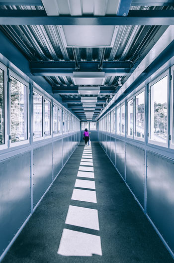 Rear view of woman walking in covered walkway