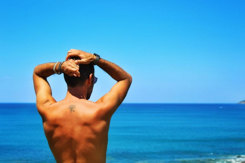 Shirtless man standing at beach against clear blue sky