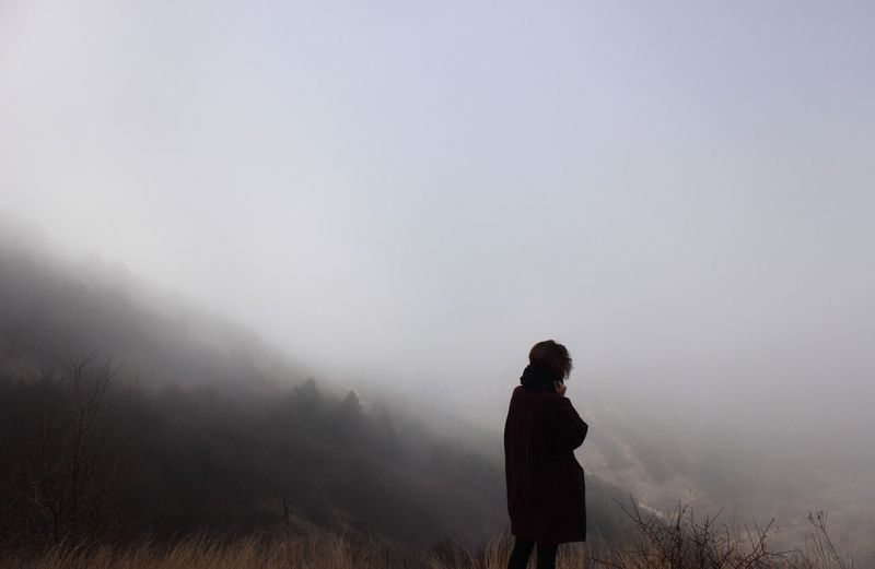 Rear view of man standing on field in foggy weather