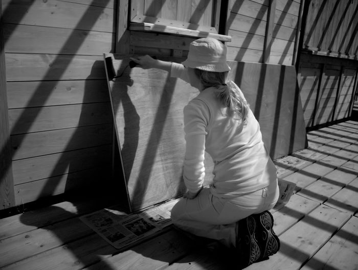 Rear view of women painting wooden plank