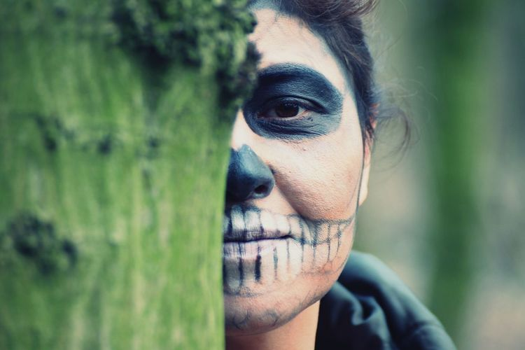Portrait Of Woman Dressed As Zombie By Tree Trunk