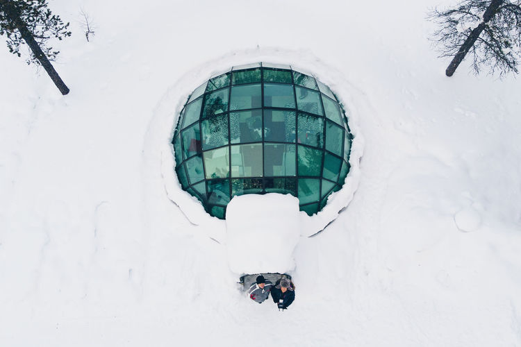 Aerial View Of Male Friends Standing At Hotel Amidst Snow Covered Field