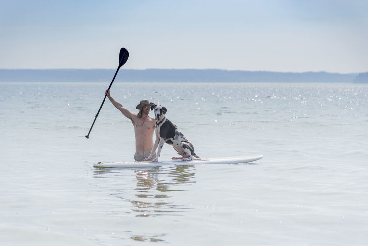 Shirtless man with dog paddleboarding in sea against sky