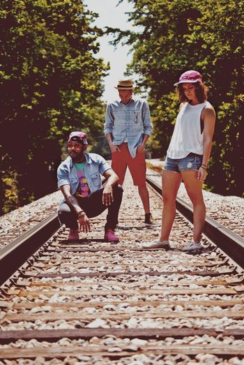 Full length of funky young friends at railroad tracks