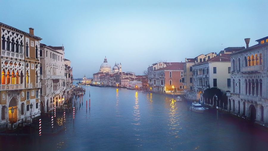Grand canal amidst buildings in city at dusk