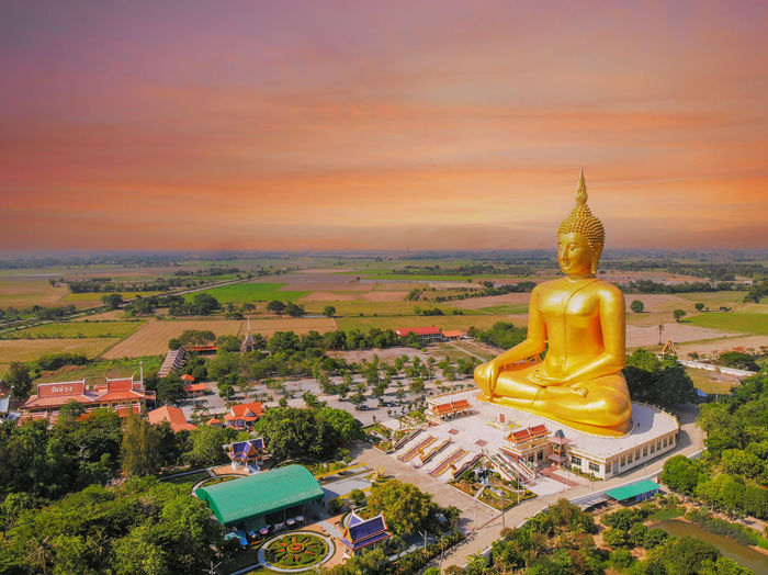 Statue of buddha against sky at sunset