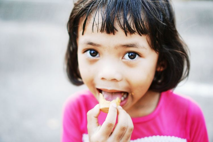 Portrait of cute girl eating food outdoors