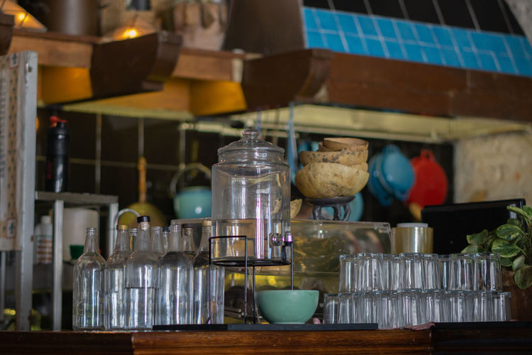 Bottles and glasses arranged on kitchen island in restaurant