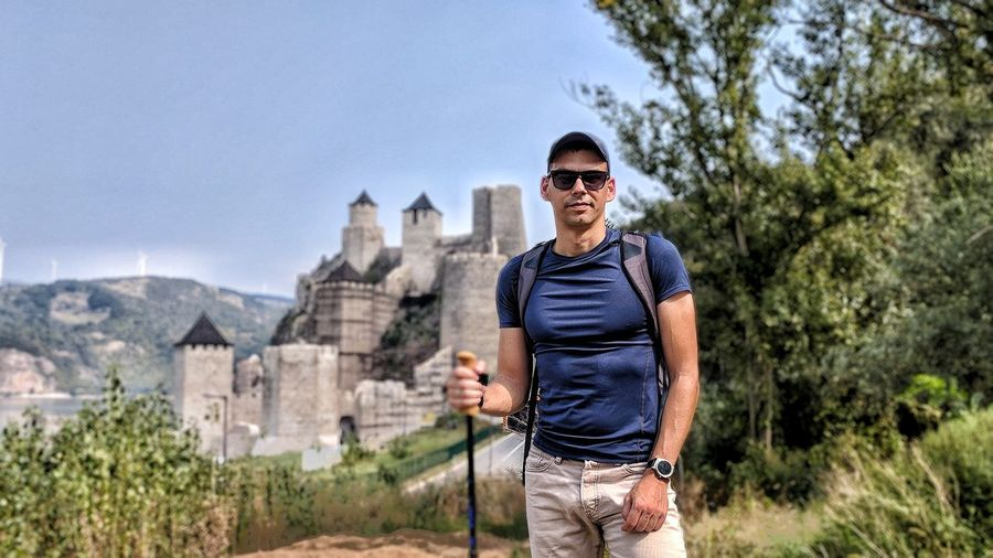 Hiker in front of fortress Serbia Castle Fortress Guy Hiking Backpack EyeEm Selects Men Standing Mountain Sky Posing Sunglasses Head And Shoulders Hiker Eyewear Visiting Clear Sky Wearing Coast Hot Pants