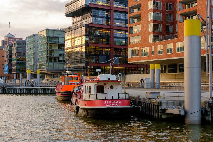 Boat moored on river against buildings in city