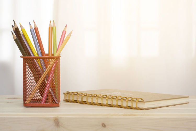 Close-up of pencils in organizer by spiral notebook on desk