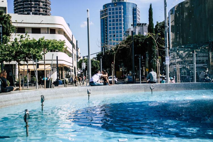 People swimming in pool against buildings in city