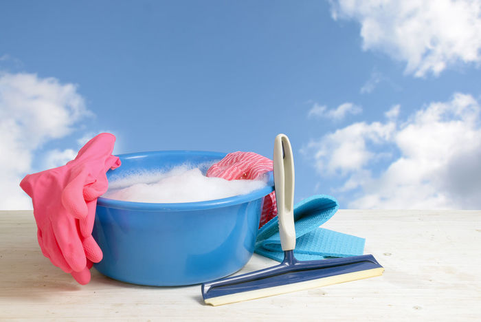 Spring cleaning, blue plastic bowl with soap foam, pink rubber gloves, rags and a window wiper on white wooden planks against a blue sky with clouds, copy space Cleaning Hygiene Blue Bowl Clear Cloth Cloud - Sky Clouds Cloves Concept Freshness No People Object Plastic Rag Rubber Sky Spring Cleaning Squeezing Wash Water Window Wiper
