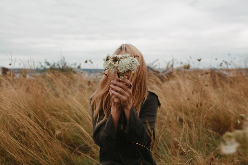 Blond woman holds bouquet of wildflowers in front of her face among grassy sand dunes. Wildflowers One Person Real People Plant Field Adult Leisure Activity Women Land Lifestyles Nature Sky Obscured Face Unrecognizable Person Holding Grass Front View Portrait Landscape Waist Up Outdoors