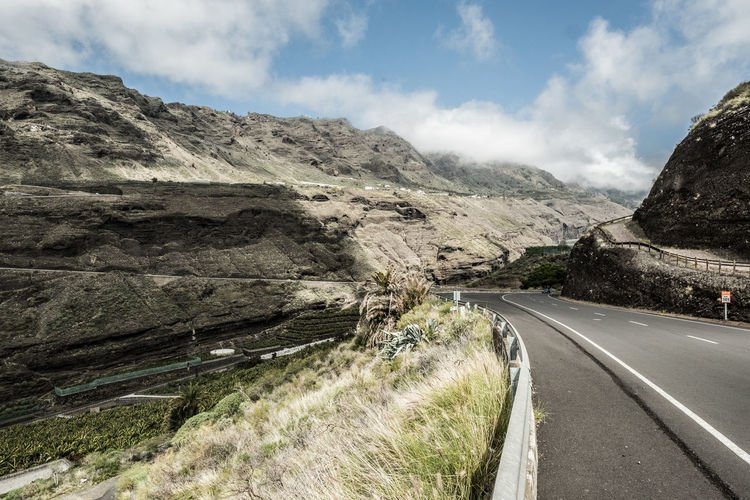 Road leading towards mountain range against sky