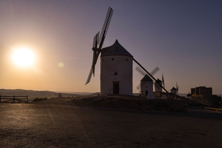 Traditional windmill by building against sky during sunset