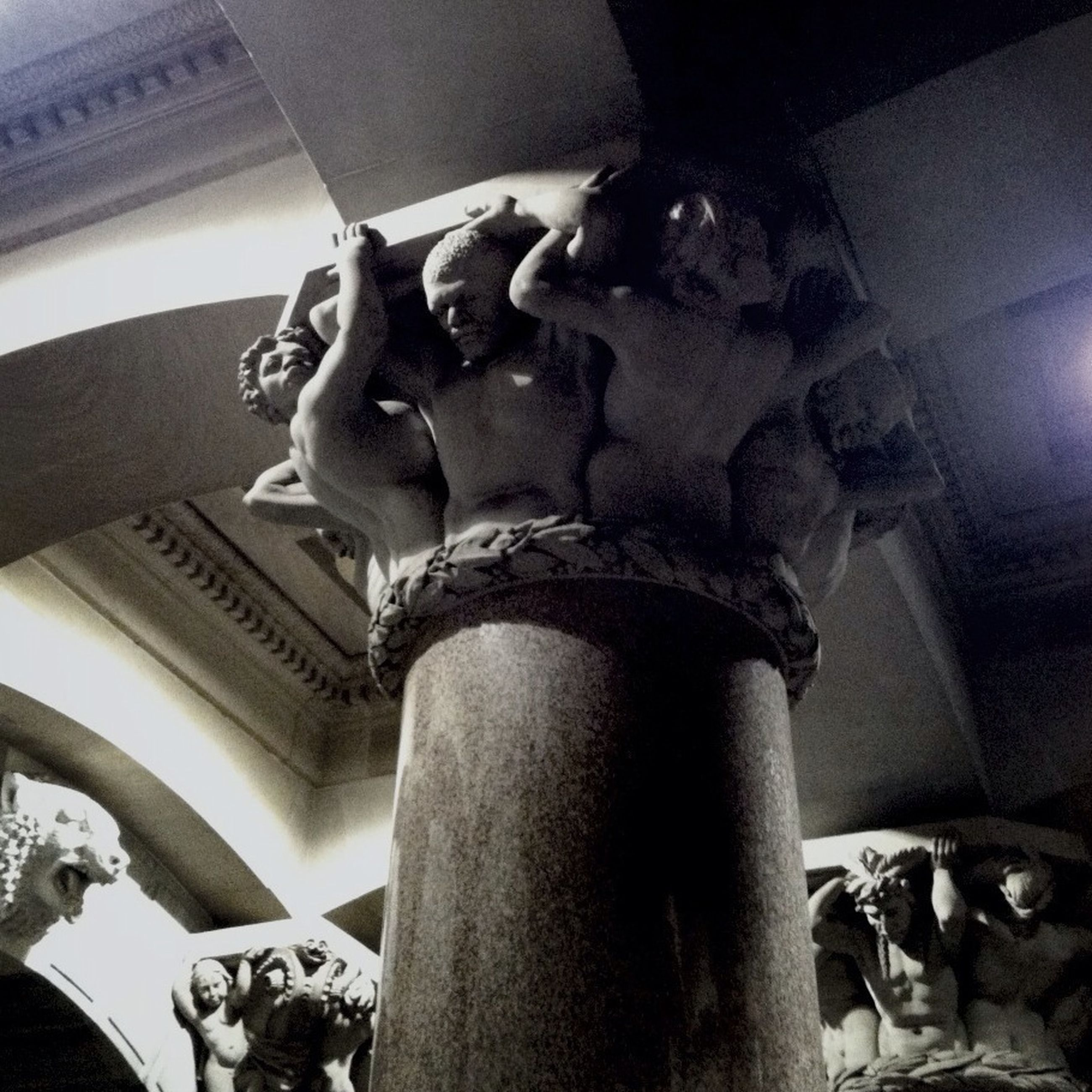 indoors, statue, sculpture, art and craft, low angle view, human representation, art, creativity, architecture, built structure, carving - craft product, history, architectural column, no people, animal representation, column, old, ceiling