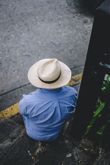 SEATED AND HATTED Asian Style Conical Hat Casual Clothing Clothing Day Full Length Hat High Angle View Leisure Activity Lifestyles Men Nature Obscured Face One Person Outdoors Real People Rear View Sitting Streetphotography Transportation Unrecognizable Person Women