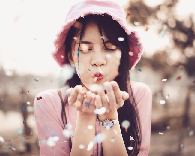 Young woman wearing hat blowing confetti