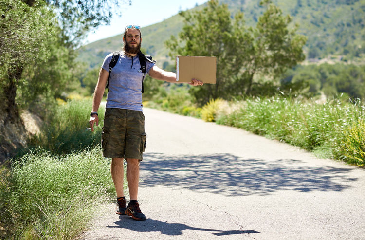 Hitch-hiking traveler with a blank cardboard sign on a mountain road. Budget travel. Auto stop Adventure Alone Auto Stop Autostop Bearded Blank Budget Traveller Caucasian Hiker Hitchhiker Hitchhiking Journey Man Mountain Road Outdoors Passenger Roadway SPAIN Summer Tourism Tourist Travel Traveler Trip Young Adult