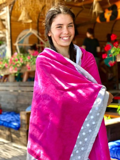 Portrait of happy girl wrapped in pink towel while standing outdoors