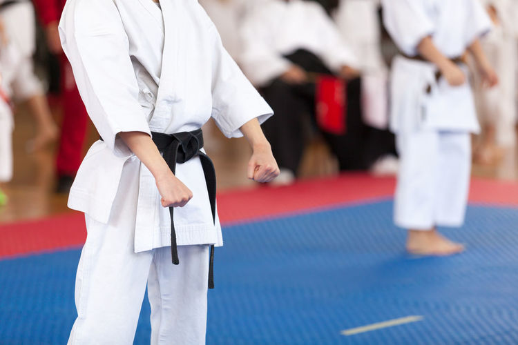 Midsection of man standing on stage during karate competition