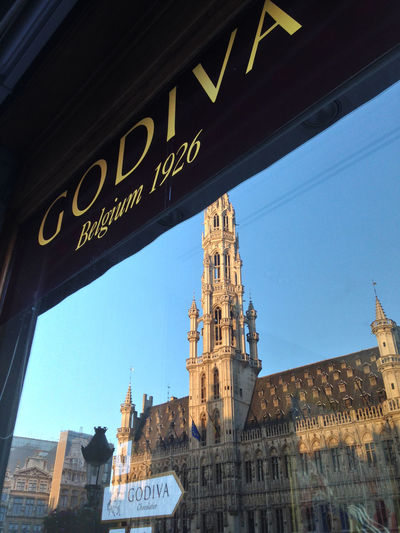 Grand Place Brussels - reflection in the window of Godiva Brussels Europe Capital Cities  Godiva Godiva Chocolate Grand Place Architecture Built Structure Building Exterior Low Angle View Travel Destinations No People Building City Text Place Of Worship History Window The Past Religion Belief Tourism Day Sky Spirituality Outdoors Clock