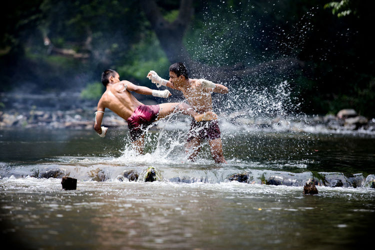 Full Length Of Shirtless Warriors Fighting In River At Forest