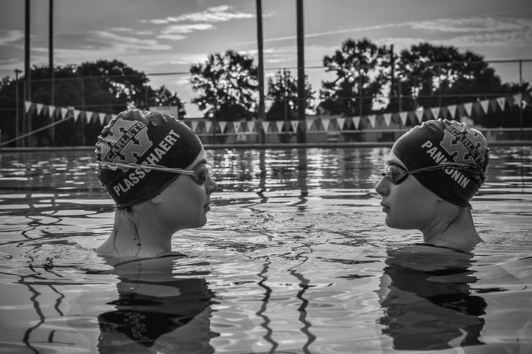 Rear view of man and woman swimming pool