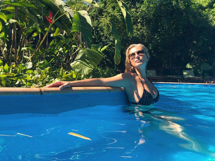 Sensuous woman looking away while standing in swimming pool
