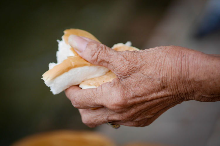 Close-up of man holding bread outdoors