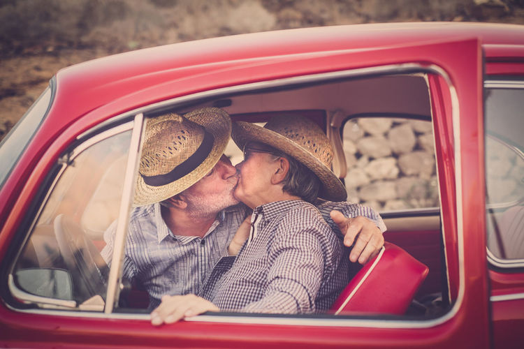 Senior Couple Kissing In Vintage Car