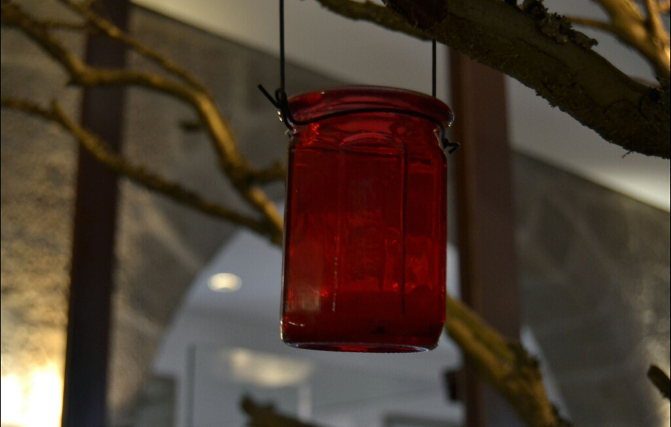 red, hanging, focus on foreground, close-up, lantern, low angle view, selective focus, indoors, built structure, no people, day, lighting equipment, wall - building feature, architecture, safety, metal, building exterior, protection, sunlight